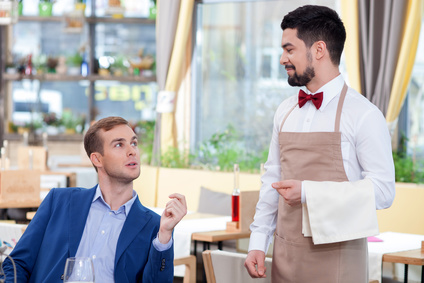 Cheerful male cafe worker is serving a customer